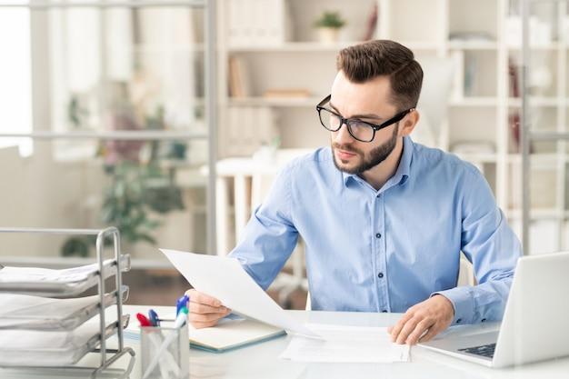 Młody biznesmen poważny w okularach, czytanie papieru finansowego lub umowy, siedząc przy biurku w biurze