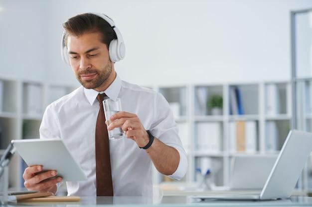 Młody biznesmen poważny w słuchawkach patrząc na ekran tabletu mając szklankę wody w miejscu pracy