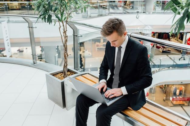 Młody biznesmen pracujący na notebooku, ubrany w czarny garnitur w centrum handlowym, usiadł, w pomieszczeniu, usiadł