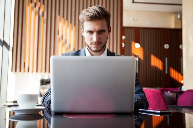 Młody biznesmen pracuje na laptopie, siedząc w holu hotelu czekając na kogoś