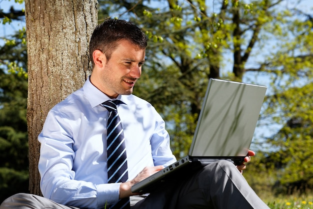 Młody biznesmen pracuje na laptopie w parku