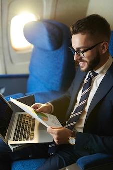 Młody biznesmen pracuje w samolocie