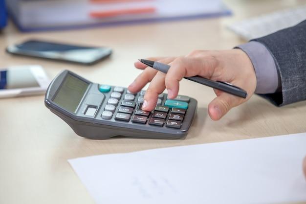 Młody biznesmen pracuje w swoim biurze i obliczania liczb