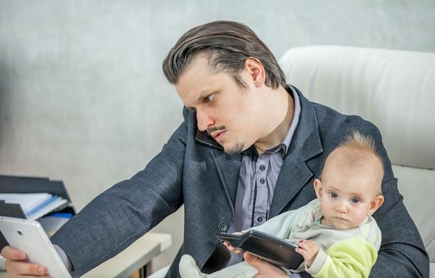 Młody biznesmen pracuje w swoim biurze i trzyma dziecko