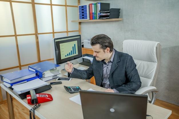 Młody biznesmen pracuje w swoim biurze - pojęcie ciężkiej pracy i porażki