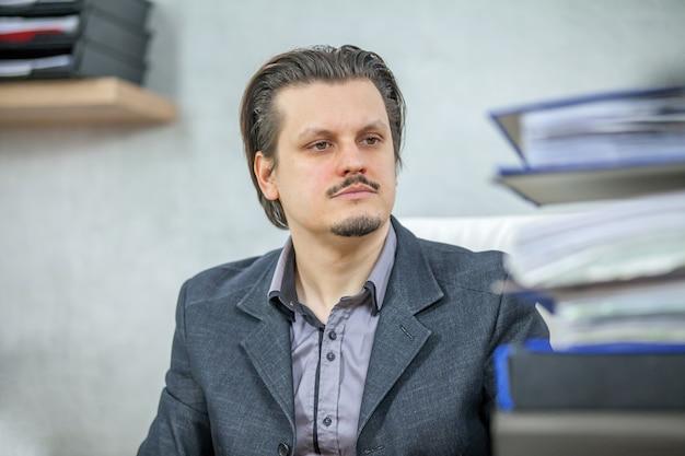 Młody biznesmen pracuje w swoim biurze - pojęcie ciężkiej pracy