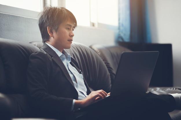 Młody biznesmen pracuje w urzędzie do inwestycji analizowanie bilansu sprawozdania finansowego firmy z komputera przenośnego.