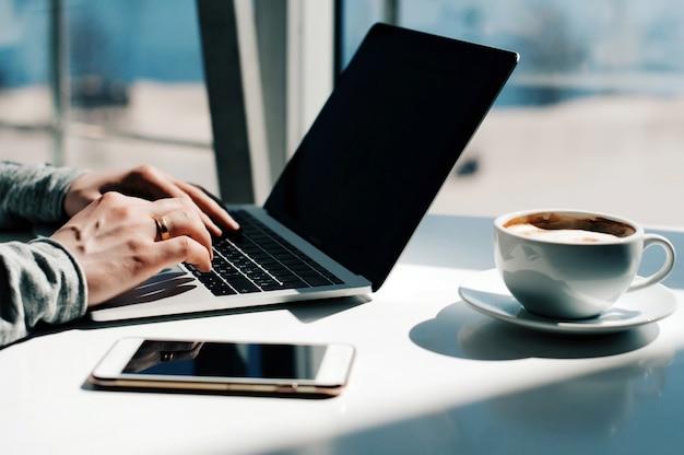 Młody biznesmen pracuje z laptopem przy biurem. człowiek za pomocą nowoczesnego laptopa