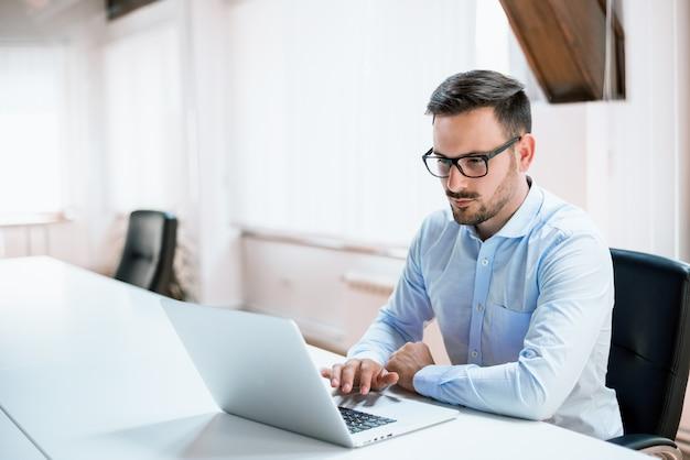 Młody biznesmen pracuje z laptopem przy biurem