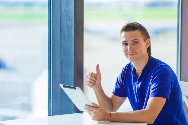 Młody biznesmen pracuje z laptopem przy lotniskową kawiarnią