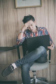 Młody biznesmen pracuje z stresem w biurze