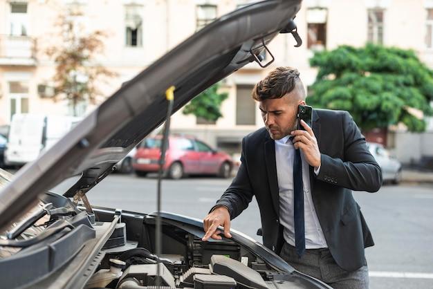 Młody biznesmen próbuje naprawić swój samochód