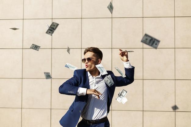 Młody biznesmen przechodzi przez dolary i tańce na ulicy