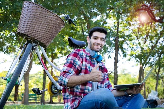 Młody biznesmen, przystojny mężczyzna siedzący obok roweru i pracujący poza biurem ze swoim ulubionym laptopem ma promienny uśmiech i jest liderem pomysły na wyobrażanie sobie i relaks w ogrodzie