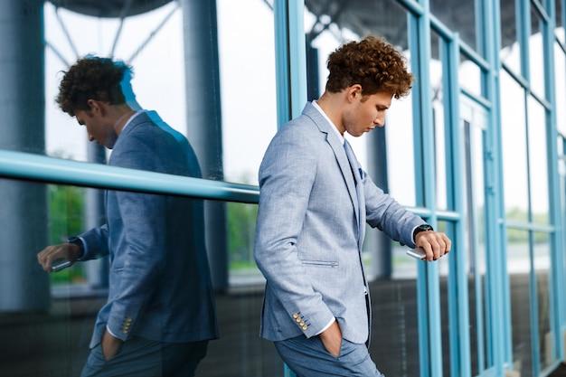 Młody biznesmen redhaired, patrząc na zegarek