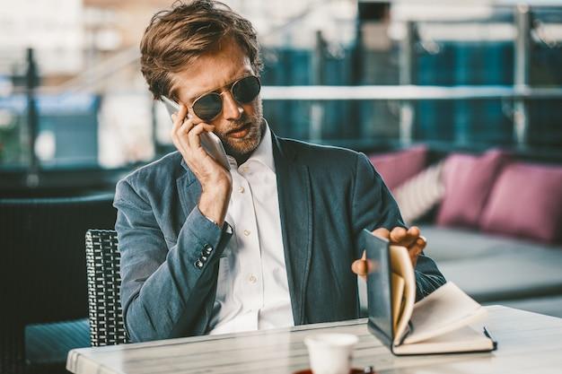 Młody biznesmen robi harmonogramowi przystawia podczas rozmowy przez telefon