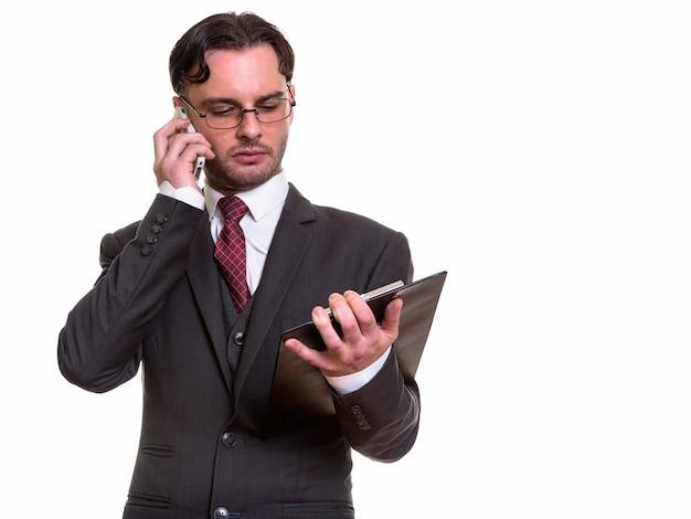 Młody biznesmen rozmawia przez telefon komórkowy podczas czytania schowka