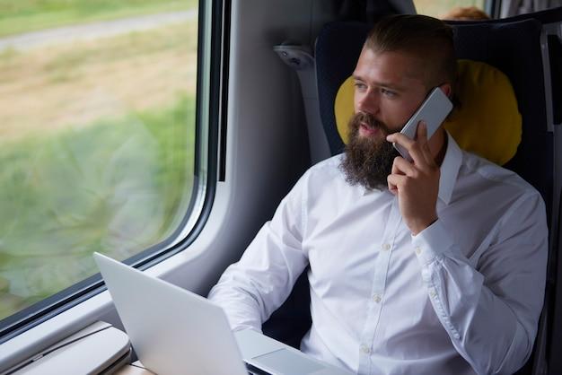 Młody biznesmen rozmawia przez telefon komórkowy w pociągu