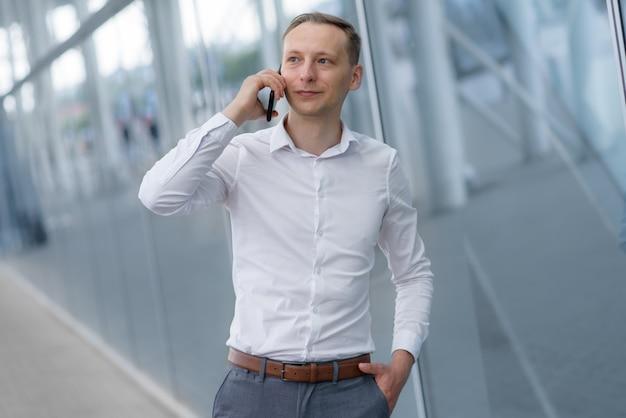 Młody biznesmen rozmawia przez telefon.