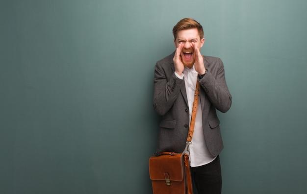 Młody biznesmen rudy krzyczy coś szczęśliwego do przodu