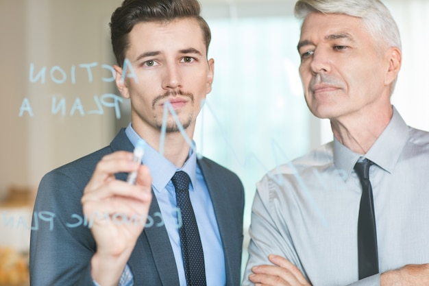 Młody biznesmen rysowanie wykresu kontrolowana przez boss