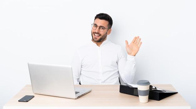 Młody biznesmen salutuje ręką z szczęśliwym wyrażeniem w miejscu pracy