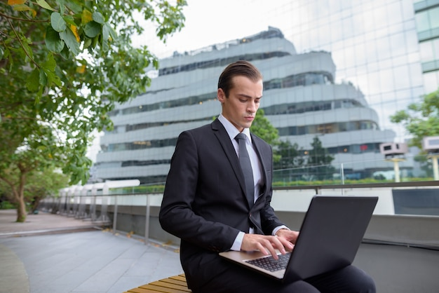 Młody biznesmen siedzi i korzystania z komputera przenośnego w mieście