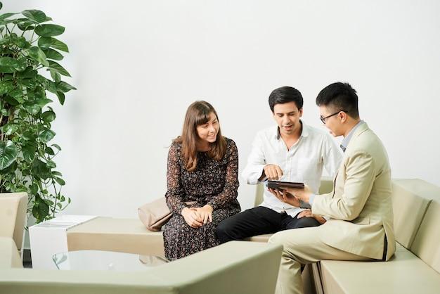 Młody biznesmen siedzi na kanapie i pokazując prezentację online na cyfrowym tablecie do pary podczas spotkania biznesowego w biurze