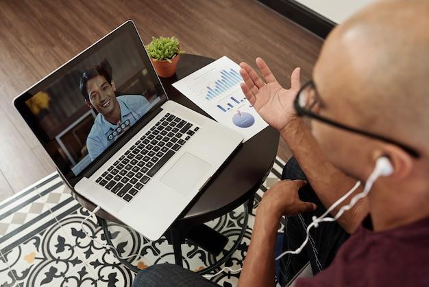 Młody biznesmen siedzi przy małym stoliku z raportem finansowym i wideo dzwoni do swojego wietnamskiego kolegi