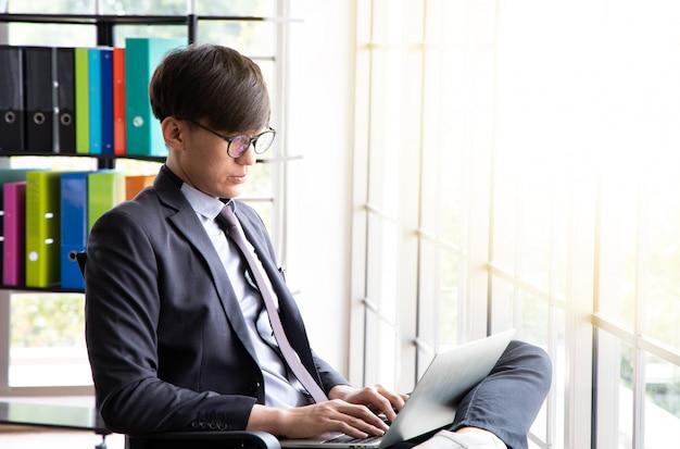 Młody biznesmen siedzieć i pracować w biurze położył laptopa na nodze.