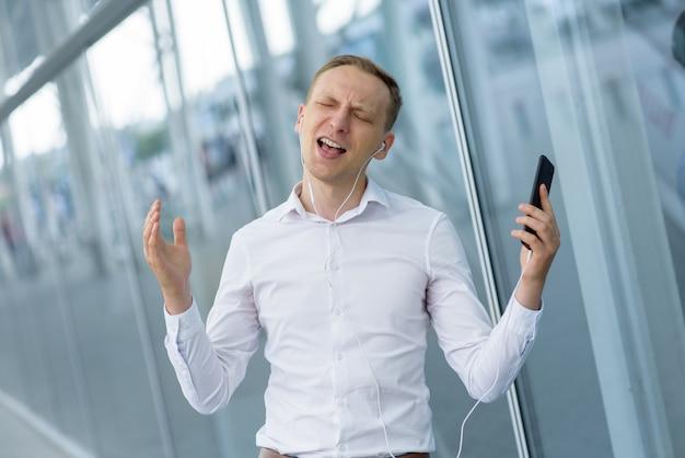 Młody biznesmen słucha muzyki na słuchawkach. mężczyzna relaksuje się po ciężkim dniu.
