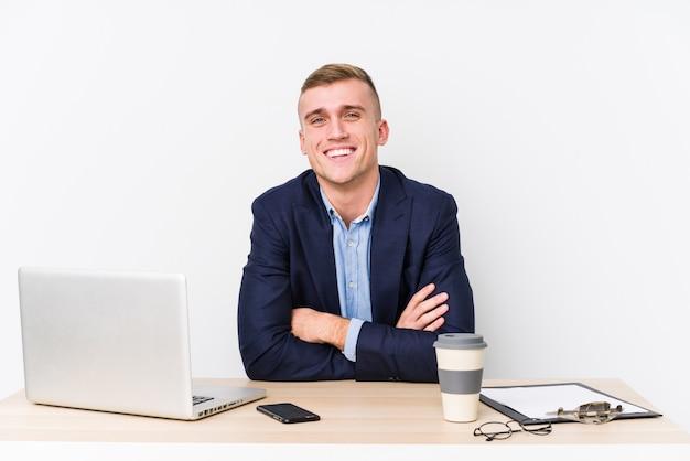 Młody biznesmen śmieje się i zabawy z laptopem.