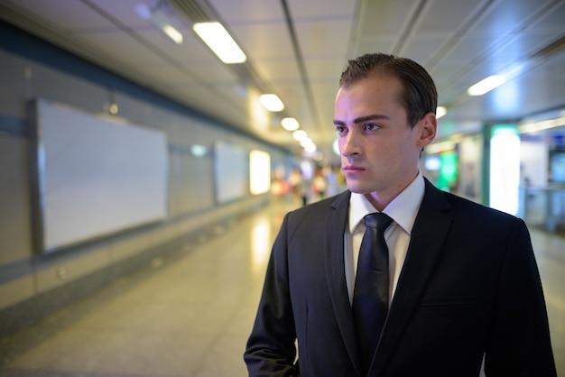 Młody biznesmen, spacery i myślenie na dworcu