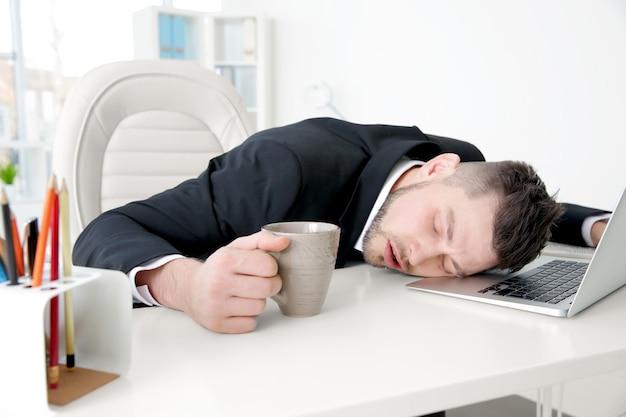 Młody biznesmen śpi na stole w miejscu pracy