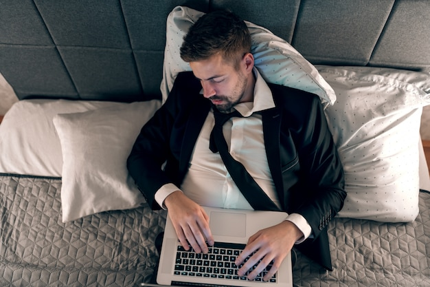 Młody biznesmen śpi w łóżku z laptopem. ręce na klawiaturze. koncepcja przepracowania.