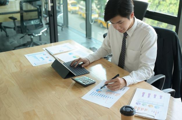 Młody biznesmen sprawdza dane na wykresie i używa laptop na biurowym biurku.
