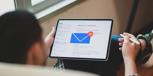 Młody biznesmen sprawdza jego emaila na pastylce