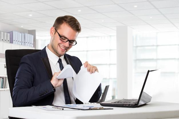 Młody biznesmen sprawdza papier beside przed laptopem