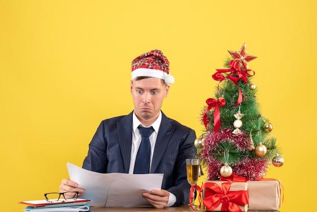Młody biznesmen sprawdzanie dokumentów siedzi przy stole w pobliżu choinki i przedstawia na żółto
