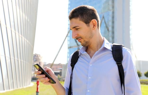 Młody biznesmen sprawdzanie swojego telefonu komórkowego w nowoczesnym mieście