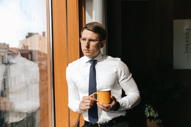 Młody biznesmen stoi przy filiżance kawy przy oknie swojego biura