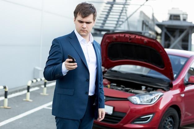 Młody biznesmen stojący przy zepsutym samochodzie i używający telefonu