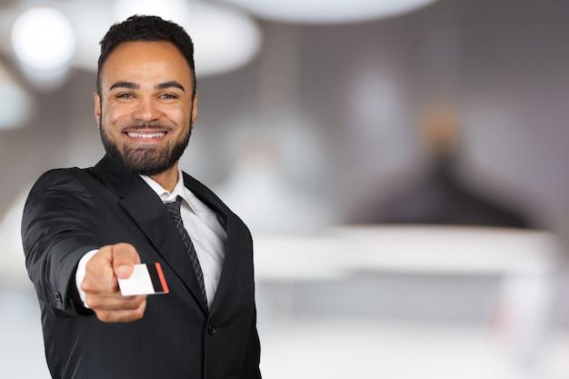Młody biznesmen sukces w stylowym czarnym klasycznym garniturze trzyma plastikową kartę kredytową