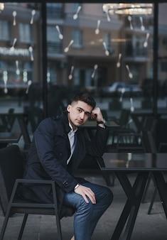 Młody biznesmen sukcesu siedzi przy stole w kawiarni w pobliżu biura