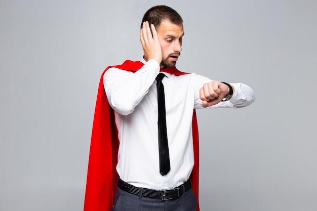 Młody biznesmen super bohatera patrzeć na zegarek późno na białym tle