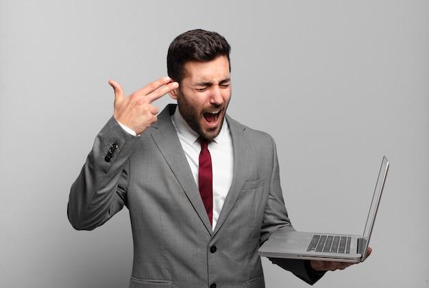Młody biznesmen szuka nieszczęśliwego i zestresowanego, gest samobójczy robi znak pistoletu ręką, wskazując na głowę i trzyma laptopa