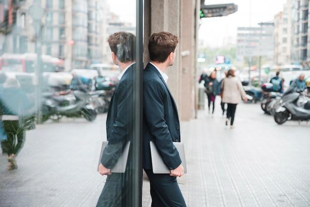 Młody biznesmen trzyma cyfrową pastylkę w ręce opiera na szkle
