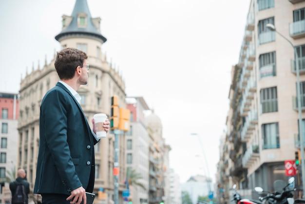 Młody biznesmen trzyma filiżankę kawy w ręku patrząc na budynki w mieście