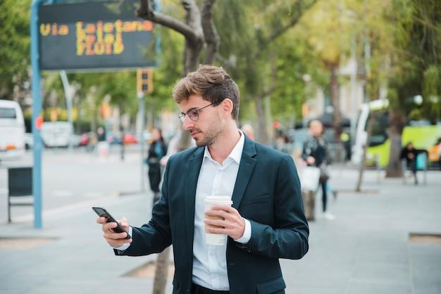 Młody biznesmen trzyma rozporządzalną filiżankę patrzeje telefon komórkowego