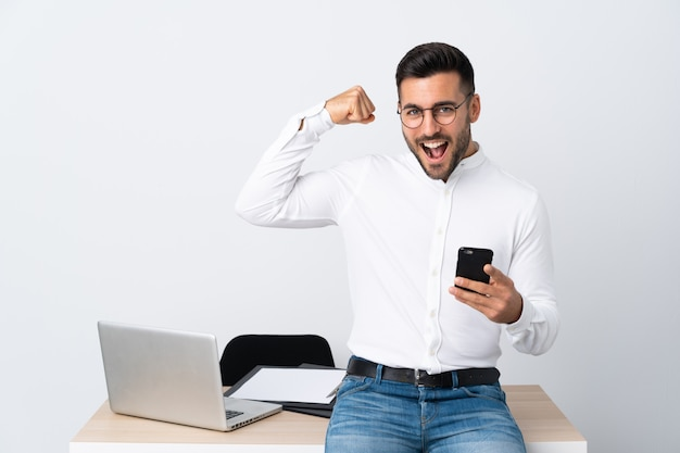 Młody biznesmen trzyma telefon komórkowego robi silnemu gestowi